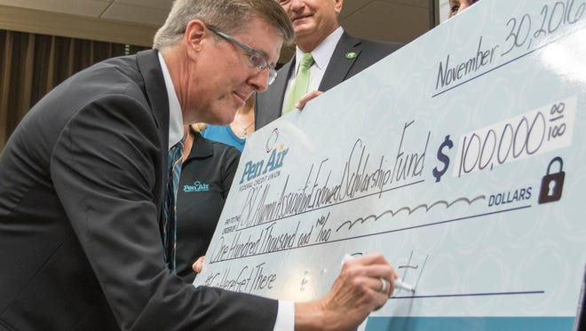 President Edward Meadows looks on as Stu Ramsey, president and CEO of Pen Air, signs a $100,000 check at Pensacola State College on Wednesday, November 30, 2016.  The gift from Pen Air is to be used for the Pensacola State College Alumni Association Endowed Scholarship Fund.
