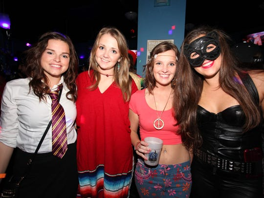 Four women celebrate Halloween.