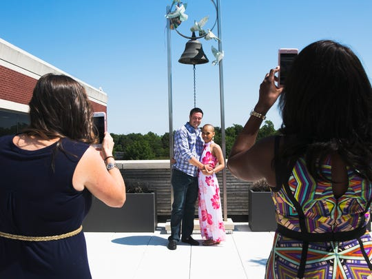 Tori Figg (left) and Mia Randolph (right) shoot portraits of Dan and Sauphia Lanning at the West Cancer Center on Monday. Sauphia was diagnosed with osteosarcoma, a rare, aggressive form of cancer, and on Monday she rang the bell at the center to signify the end of her active treatments.