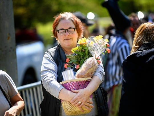 Susan Hudson McBride carries flowers in her picnic