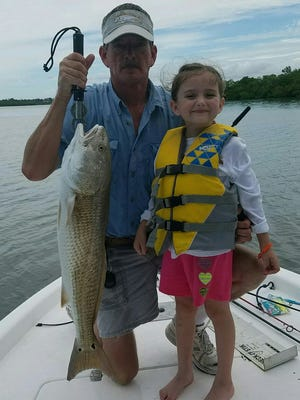 Bill Pfaff and his granddaughter, Elizabeth, show off a red fish that they caught on a jig with a gulp swimming mullet.