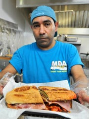 Manolo Mendes, Taqueria Tres Hermanos' chef, prepares one of the restaurant's most popular sandwiches, the Torta Hawaiiana.