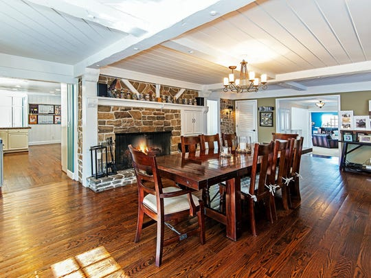 Polished oak floors and a fireplace with a stone surround distinguish the dining room at 866 Skyline Blvd.