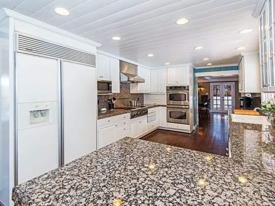 The kitchen at 866 Skyline Blvd. features speckled granite countertops, a stainless steel hood, and cabinets and appliances with crown molding.