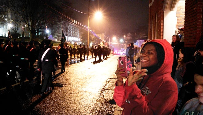 Carlyssa LeBeauf, a junior at Mary Baldwin College, waves to Virginia Women's Institute for Leadership cadets as they march along West Frederick Street during the Staunton Christmas Parade on Monday, Nov. 30, 2015.