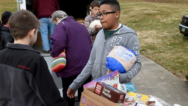 "Seventh-grader Kason Hart of C.F. C F Richards Christian School carries a frozen turkey breast that goes with a food box being given to a family. Students from the school assisted volunteers at the Staunton Seventh-Day Adventist Church in handing out over 125 boxes of food to those in need on Tuesday, Dec. 13, 2016. ""It's fun to be able to give back to the community because they've done so much for us,"" said Kason, ""and I just want to support everybody."""