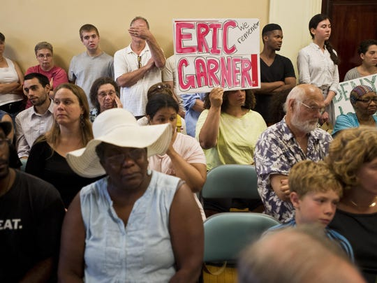 "Vicki Garrison, center, holds a sign that reads, ""We remember Eric Garner"" at a Burlington City Council meeting Monday night as the police chief nominee, New York Police Department Deputy Inspector Brandon del Pozo, addressed the council. Dozens attended the meeting holding signs opposing del Pozo's appointment. Eric Garner died in New York City in 2014 after a police officer put him in what has been described as a ""chokehold."""