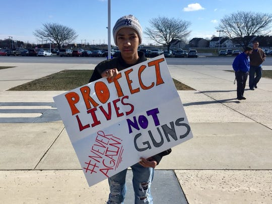 "Middletown High School junior Jordan Vaughan holds a sign reading ""Protect lives, not guns"" during a walkout on March 14. Less than three months later, a student at the school was arrested for pointing a gun at another classmate in the school's bathroom."