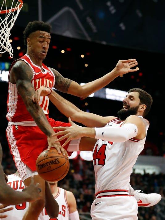Atlanta Hawks forward John Collins (20) blocks Chicago Bulls forward Nikola Mirotic's (44) shot during the second half of an NBA basketball game Saturday, Jan. 20, 2018, in Atlanta. Chicago won 113-97. (AP Photo/John Bazemore)