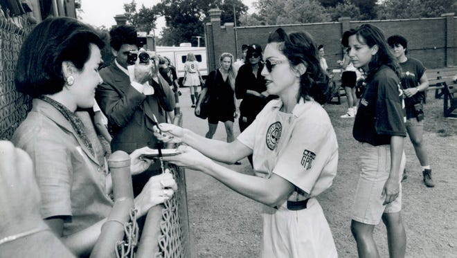 "Madonna, right, signs autographs for members of the media during filming of ""A League of Their Own"" at Bosse Field in Evansville, Ind., on Sept. 9, 1991."