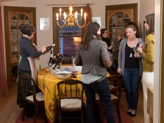 Erin Grace (left) reads a wine label at a gathering
