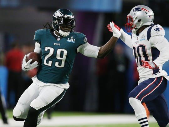 Philadelphia Eagles running back LeGarrette Blount (29) carries the ball as New England Patriots strong safety Duron Harmon (30) defends  during the first quarter in Super Bowl LII at U.S. Bank Stadium.