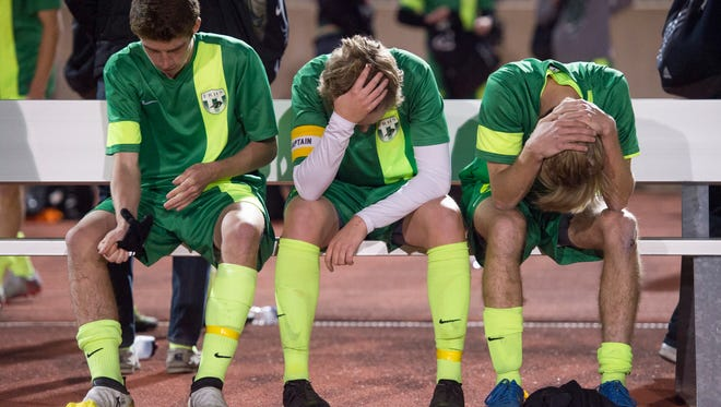 Fossil Ridge High School soccer players Tyler Hause, Matthew Wilhelm and Sam Goulding react to a 3-1 loss against Boulder in a state semifinal game at Legacy Stadium in Aurora Wednesday.