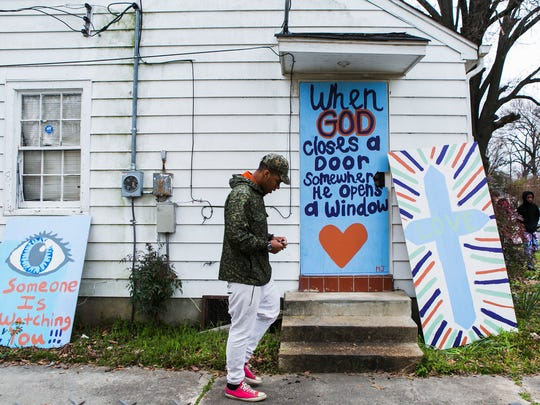 March 16, 2017 - Douglass High School senior Dion Vanhook, 18, passes decorated plywood as he and other volunteers board up a vacant house on Manhattan Ave. in the Douglass neighborhood on Thursday morning. About 60 students from Douglass and Kingsbury high schools, along with volunteers from other youth groups spent most of their Spring Break fighting blight in North Memphis.