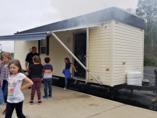 Students evacuate the trailer after simulated smoke
