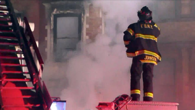 This photo provided by WPIX-11 shows New York firefighters at the scene of a raging fire at an unoccupied residential building being used as a film set in the Harlem section of New York on Thursday, March 22, 2018.