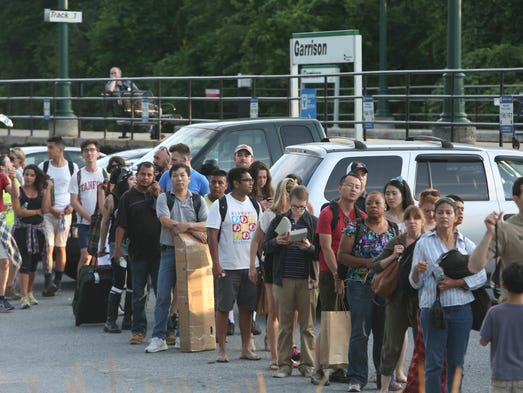 Hundreds of train passengers wait on lines to board buses at the Garrison train station after a rock slide on the railroad tracks between Peekskill and Garrison forced the closure of both north and southbound tracks July 19, 2014.