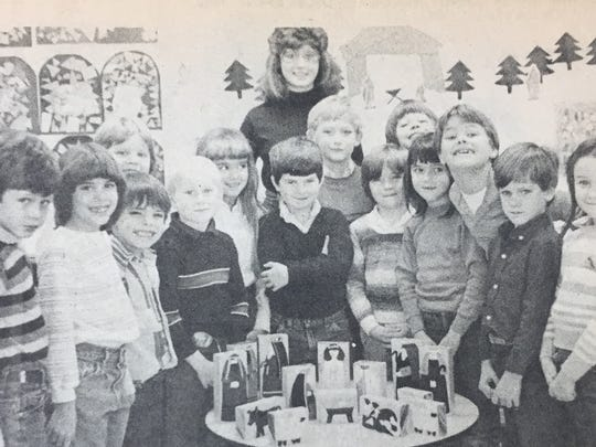 First and second grade students at St. Agnes School in Uniontown pose with the nativity scene they made in December 1985. The scene was won by Stacey Crowdus, an eighth grader at the school who is pictured in the back.