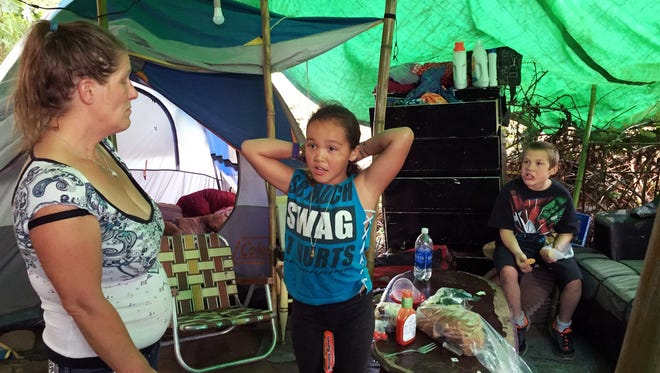 In this Aug. 10, 2016 photo, Deitra Schmer watches as her granddaughter, Andrea Brown, brushes her hair in Schmer's tent in a homeless encampment along the Springwater Corridor bike and pedestrian trail in Portland.
