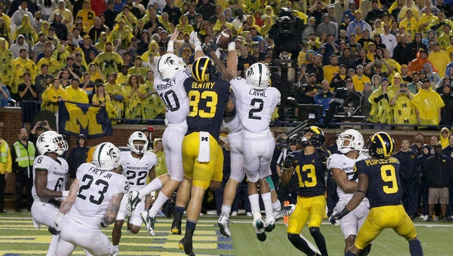 Michigan and Michigan State players jump for the football on the final play of the game at Michigan Stadium in Ann Arbor on Oct. 7, 2017. The pass fell to the ground, giving Michigan State the win, 14-10.
