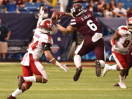 Mississippi State Bulldogs wide receiver Donald Gray (6) makes a catch in front of Miami Redhawks defensive back Heath Harding (24) during the second half at Tropicana Field. The Mississippi State Bulldogs defeat the Miami Redhawks 17-16. Mandatory Credit: Jasen Vinlove-USA TODAY Sports