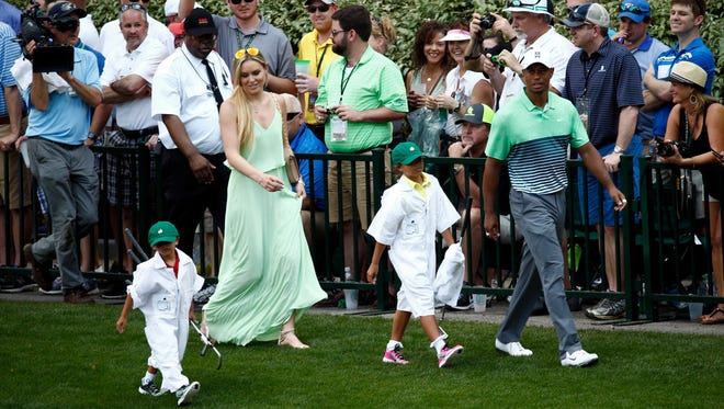Tiger Woods walks with his children, Sam and Charlie, and girlfriend Lindsey Vonn to the 9th green during the Par 3 Contest prior to the 2015 The Masters golf tournament at Augusta National Golf Club.