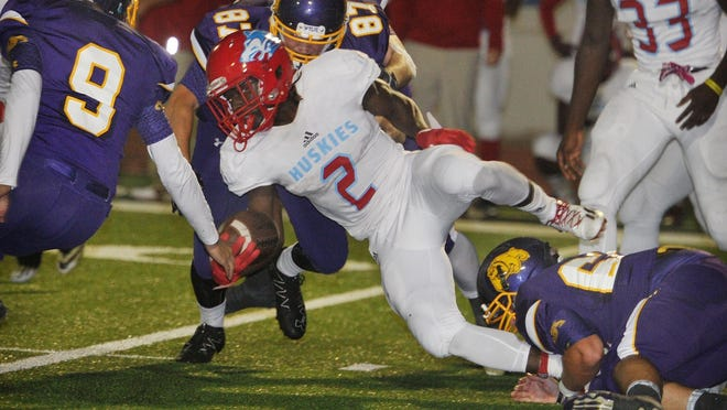 Hirschi junior Gerrick McKinney (2) struggles for yardage while being tackled by several Abilene Wylie defenders Friday night in Graham. Hirschi lost the bi-district playoff game, 45-9.