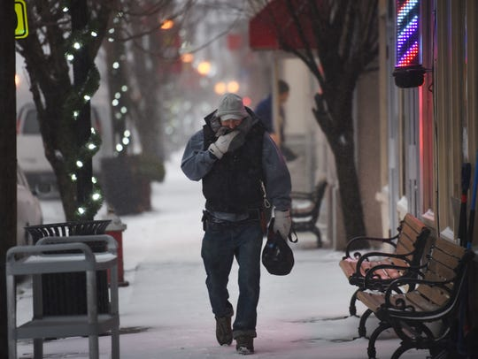 A man muffles himself against the wind and snow as