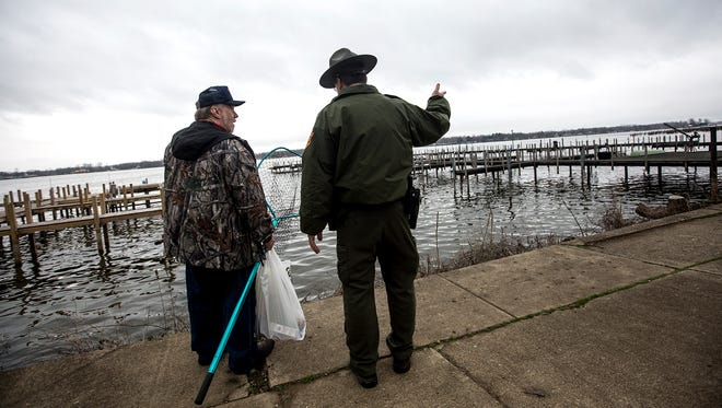 Buckeye Lake State Park Manager, Jason Wesley, out on his daily inspection of Buckeye Lake dam talks with a fisherman about where he can and cannot fish.