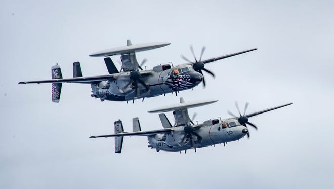 Two of the 'Black Eagles' E-2C aircraft fly in formation during a change of command ceremony above the USS Carl Vinson. The Black Eagles, whose official name is Carrier Airborne Early Warning Squadron (VAW) 113, are deployed with the aircraft carrier in the Western Pacific region.