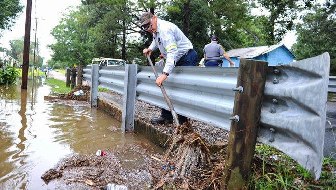 Richard Doty works to clear debris from bridge as heavy rain causes flash flooding in Carencro, LA.- Thursday, June 29, 2017.