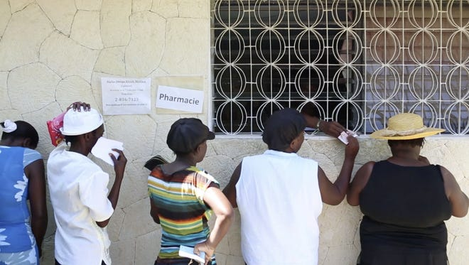 Patients wait at the old Alpha Omega Ministry pharmacy in Cabaret, Haiti. Asheville's Mercy Urgent Care has played a huge role in the helping the island clinic go from a makeshift medical center (pictured here) to a fully functional facility.