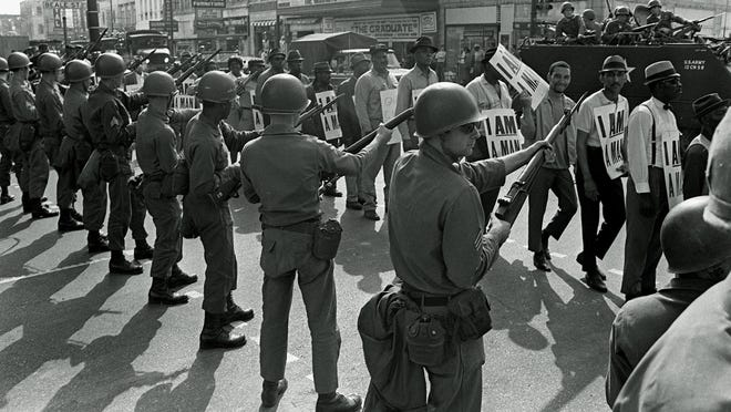 Striking sanitation workers and their supporters are flanked by bayonet-wielding National Guard troops and armored vehicles during a march on City Hall in Memphis on March 29, 1968, one day after a similar march erupted in violence, leaving one person dead and several injured.