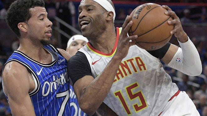 Atlanta Hawks forward Vince Carter (15) drives to the basket against Orlando Magic guard Michael Carter-Williams (7) during the first half of an April 2019 NBA basketball game. Carter announced his retirement from the NBA on Thursday.