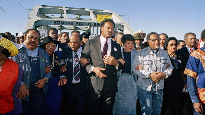 Civil rights figures lead marchers across the Edmund Pettus Bridge during the recreation of the 1965 Selma to Montgomery march in Selma, Alabama, March 4, 1990. From left are Hosea Williams of Atlanta, Georgia Congressman John Lewis, Rev. Jesse Jackson, Evelyn Lowery, SCLC President Joseph Lowery and Coretta Scott King (glasses).