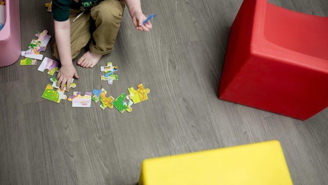 A child with autism is shown playing with a puzzle at an Austin facility offering therapy. At other facilities providing residential care for people with autism, residents have not been able to have visitors for months because of the coronavirus pandemic.