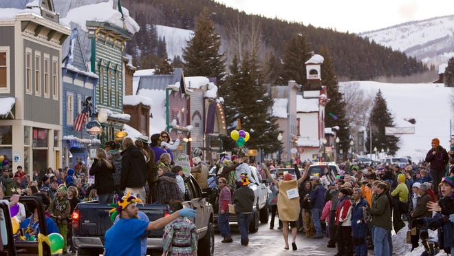 A crowd gathers on Elk Avenue in Crested Butte during a 2009 Mardi Gras parade celebration.
