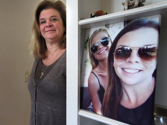 Jennifer Stalker, 46, at her home in Grosse Pointe on Wednesday, March 11, 2015. To her right is a photo of her daughters Paige, 16, in the foreground and Madison, 21, in the back taken last thanksgiving while the family visited Disney world. To the left is a large photo of Paige in the family room. Stalker is organizing a walk on May 2nd to bring awareness to violence and encourage neighborhood unity in honor of her daughter Paige Stalker who was 16 when she was killed in Detroit December of 2014. Jessica J. Trevino/Detroit Free Press