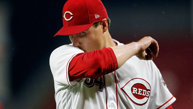 Cincinnati Reds starting pitcher Homer Bailey (34) wipes his face as he leaves the mound after the top of the first inning of the MLB National League game between the Cincinnati Reds and the Chicago Cubs at Great American Ball Park in downtown Cincinnati on Friday, May 18, 2018. After three innings the Cubs led 4-0.