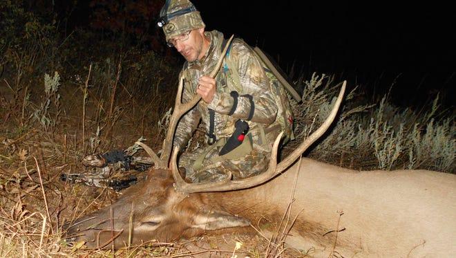 Chris White of Ohio admires the bull elk he arrowed Sept. 16 in southeastern Idaho.