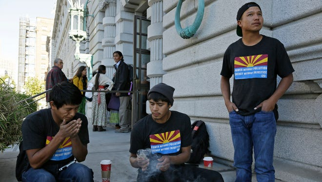 Navajo youths from left, Robert Yazzie, Sedate Tsosie and Sheldon Natoni burn sage as tribal members in the background enter the United States Court of Appeals for the Ninth Circuit in San Francisco on Friday, Nov. 18, 2016. Thirty Navajo youths have traveled from their reservation in Arizona to San Francisco to protest a federal decision that would allow a massive coal-fired power near their homes to bypass pollution-control regulations for the next several decades.