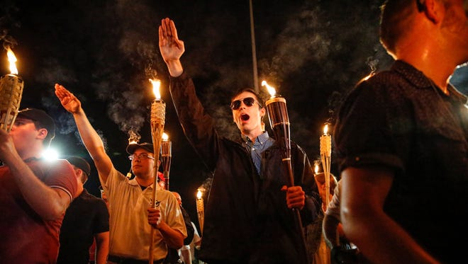Multiple white nationalist groups march with torches through the UVA campus in Charlottesville on Aug. 11, 2017. When met by counter protesters, some yelling