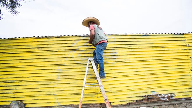 Enrique Chiu, a Mexican artist based in Tijuana, paints the border wall separating Mexico and the U.S. in Tecate, Mexico. Chiu has painted along the border from Tijuana all the way east into Mexicali and plans to paint all the way to the Gulf of Mexico where the border ends on the eastern part of both nations.
