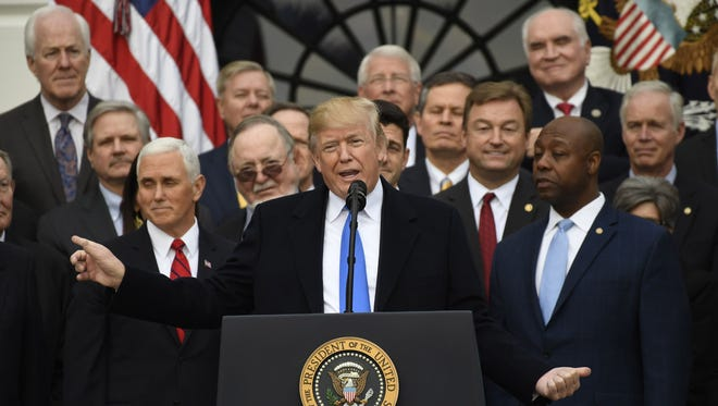 President Donald Trump, flanked by Vice President Mike Pence (L), speaks about the passage of tax reform legislation on the South Lawn of the White House in Washington, DC, December 20, 2017.