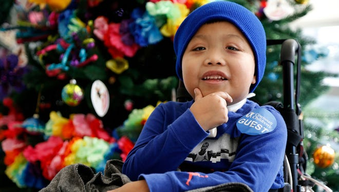 Ricky Solis, 6, of Springdale, Ohio, smiles as his mother speaks Jan. 3, 2018, at Cincinnati Children's Hospital's Liberty Campus in Liberty Township, Ohio. Ricky became paraplegic after a driver crossed lanes and struck Solis and his mother, Sandra Mendez, in their car in February 2017.