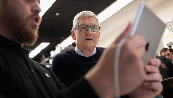 Apple CEO Tim Cook gets a demonstration of an app during an event held to introduce the new 9.7-inch Apple iPad at Lane Tech College Prep High School in Chicago, March 27, 2018.