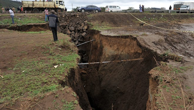 Vehicles drive next to a deep chasm on a repaired road that had been washed away during a heavy downpour at Maai-Mahiu, around 33.5 miles southwest of capital of Nairobi on March 15, 2018.