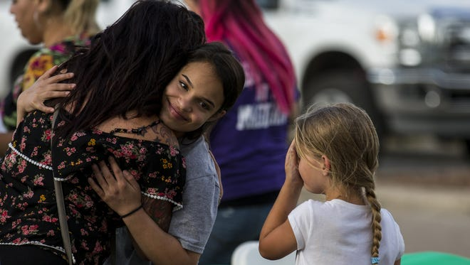 Brittany Roach (left) hugs Meah Salinas, 13, on May 19, 2018, during a community dinner in Santa Fe, Texas, a day after a shooting left 10 people dead at Santa Fe High School.