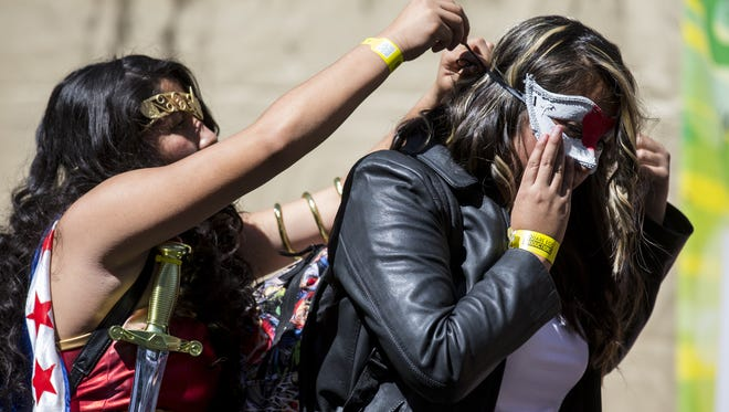 Savana Rodriguez, 13, helps Kaitlin Velasco, 14, put on a mask during Day one of Phoenix Comic Fest on Thursday, May 24, 2018 at Phoenix Convention Center in Phoenix.