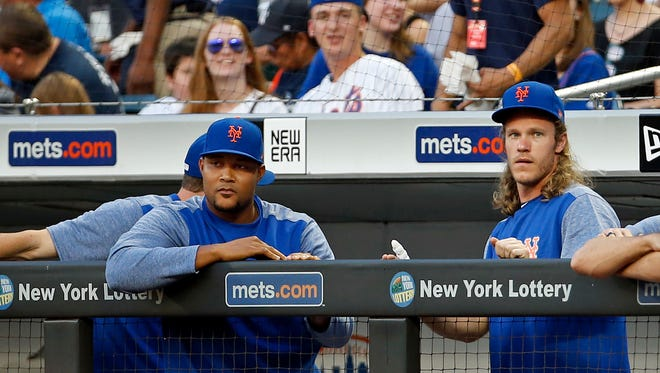 New York Mets pitcher Jeurys Familia, left, and pitcher Noah Syndergaard look on from the dugout during the third inning of a baseball game against the New York Yankees, Friday, June 8, 2018, in New York.